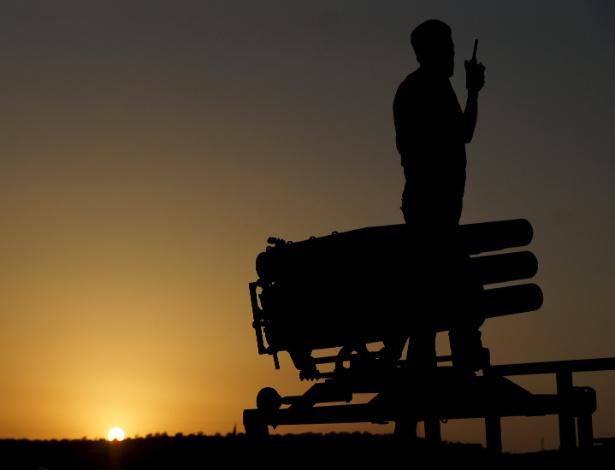 Soldado do Exército Livre da Síria conversa por walkie-talkie perto de lançador de foguetes durante preparação de ataque às forças que apoiam Bashar al Assad