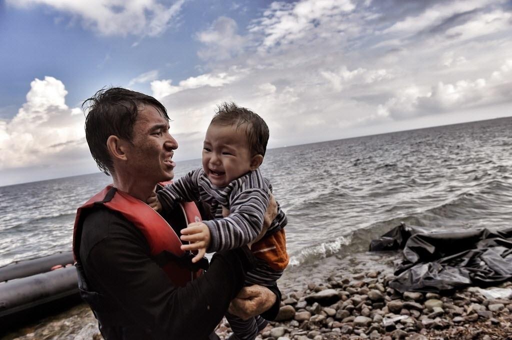28.set.2015 - Refugiado chega com bebê na costa da ilha de Lesbos, na Grécia, após cruzar o mar Egeu, saindo da Turquia. Ao defender que pessoas circulem livremente pelo globo, a presidente Dilma Rousseff afirmou que o Brasil recebe