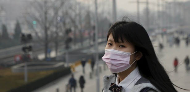 Jovem usa máscara para se proteger da névoa de poluição em Beijing, na China