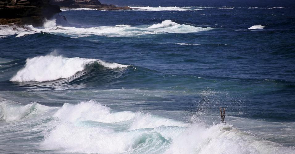 27.fev.2016 - Surfista cai da prancha após manobrar em onda durante ressaca na praia de Bronte, em Sydney. Nas últimas horas toda a costa leste da Austrália apresenta condições de surf perigosas devido às grandes ondas, resultado do ciclone Winston, que atingiu Fiji na semana passada, deixando 42 mortos