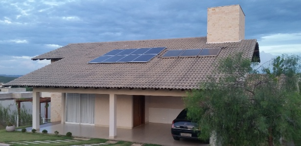 Casa equipada com painéis de microgeração de energia (e) e aquecimento solar (d)