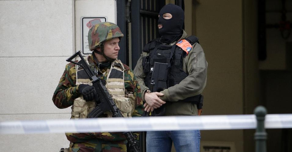 24.mar.2016 - Policial e militar fazem guarda diante da Câmara do Conselho de Bruxelas, durante as investigações dos ataques terroristas de Paris e Bruxelas. Mais de 30 pessoas foram identificadas como envolvidas em uma rede por trás dos ataques de Paris, realizados em 13 de novembro, com ligações para os atentados desta semana em Bruxelas