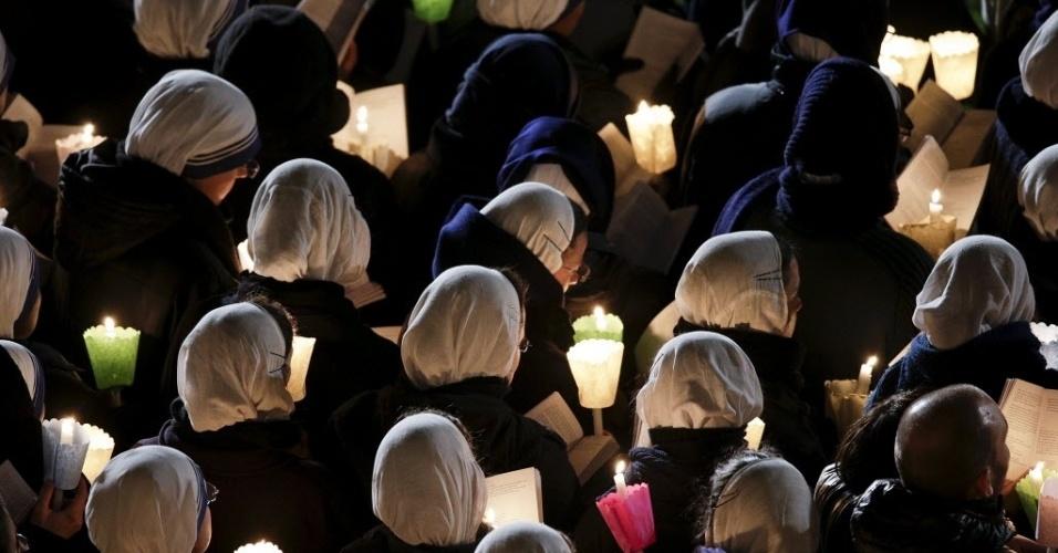 25.mar.2016 - Freiras seguram velas enquanto o papa Francisco lidera a Via-Crúcis em frente ao Coliseu, em Roma