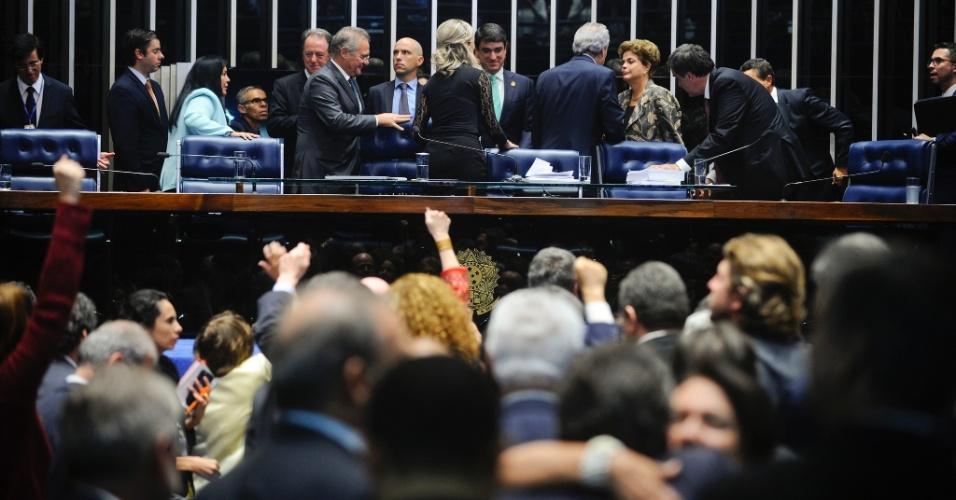 30.ago.2016 - A presidente afastada, Dilma Rousseff, cumprimenta o presidente do julgamento do impeachment, Ricardo Lewandowski, enquanto senadores aliados aplaudem e gritam palavras de ordem no final da sessão no Senado Federal