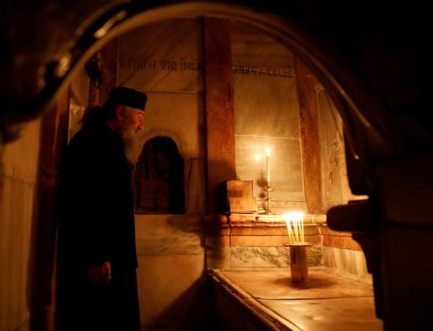 Sacerdote grego ortodoxo na recém-restaurada edícula, a estrutura antiga que abriga o túmulo (em sua frente) onde, de acordo com a fé cristã, o corpo de Jesus Cristo foi sepultado, na Igreja do Santo Sepulcro, na Cidade Antiga de Jerusalém