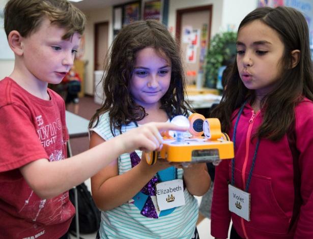 Da esquerda para a direita, Declan Lewis, 8, Elizabeth Sheldon, 7, e Violet Smith, 7, com o robô Kibo no acampamento de verão DevTec, da Tufts University, em Medford (EUA)