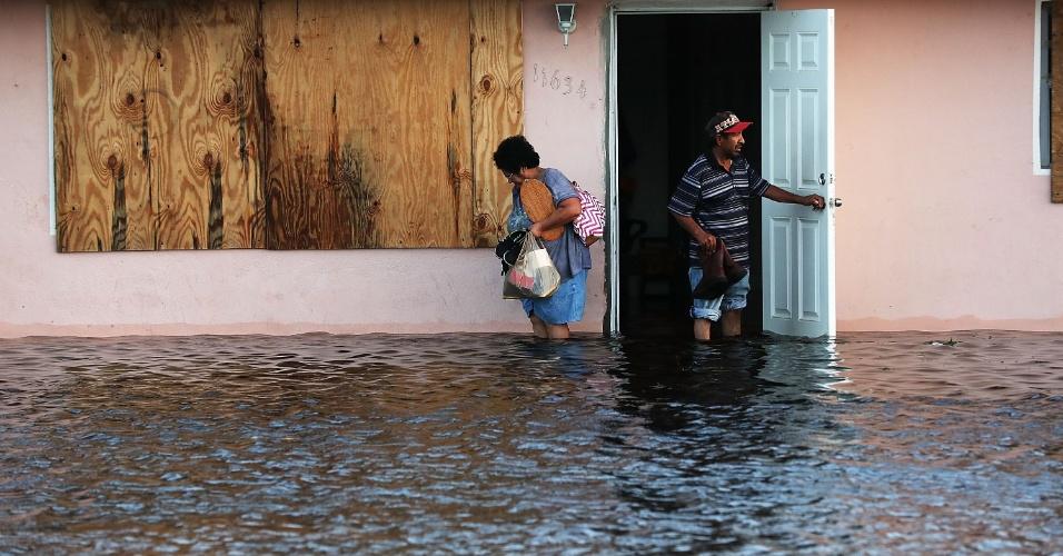 11.set.2017 - Casal se depara com enchente ao tentarem sair de casa em Fort Myers, na Flórida (EUA)). A região foi devastada pela passagem do furacão Irma