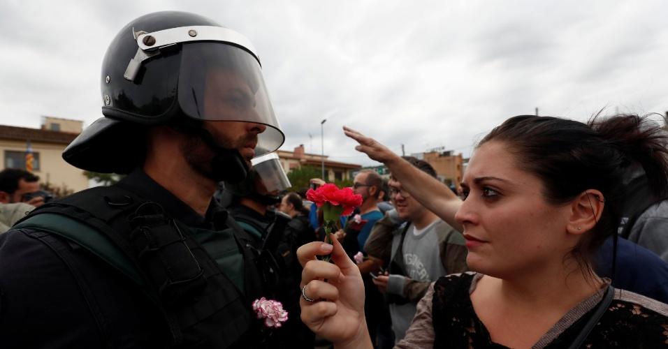 1.out.2017 - Mulher oferece flor a oficial da Guarda Civil Espanhola após o bloqueio do centro de votação em Sant Julia de Ramis