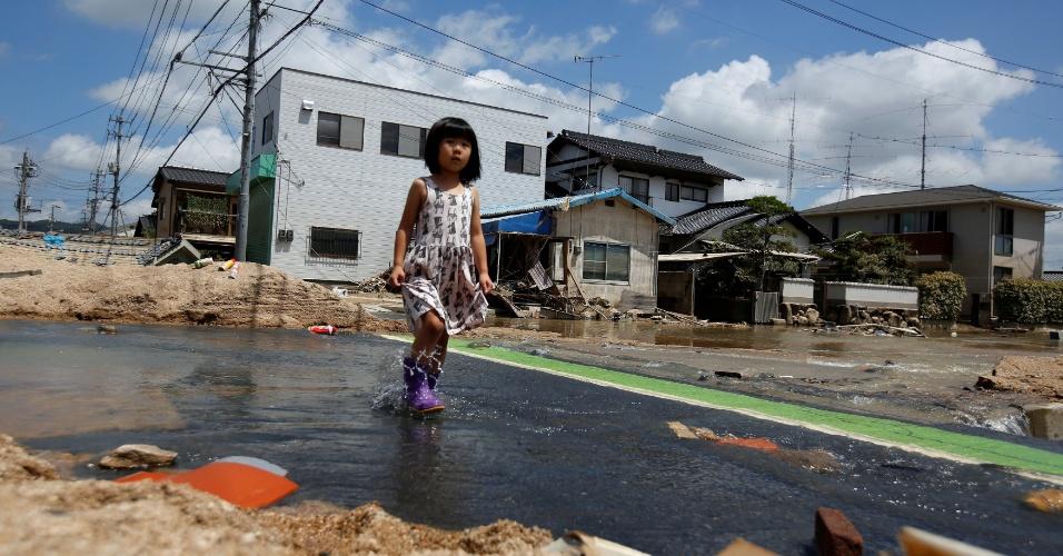10.jul.2018 - Menina caminha por área afetada pela inundação na cidade de Kurashiki