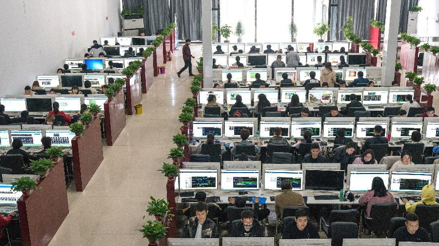 Trabalhadores na sede da Companhia de Tecnologia Ruijin, em Jiaxian, na província chinesa de Henan - Yan Cong/The New York Times
