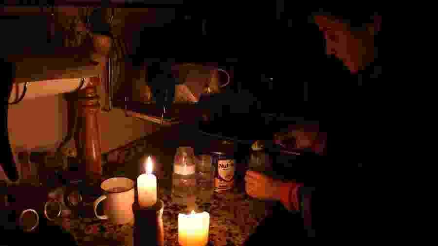 Mulher prepara leite sob a luz de velas, em Montevidéu, durante apagão que deixou o Uruguai e a Argentina sem energia na manhã deste domingo - Miguel Rojo/AFP