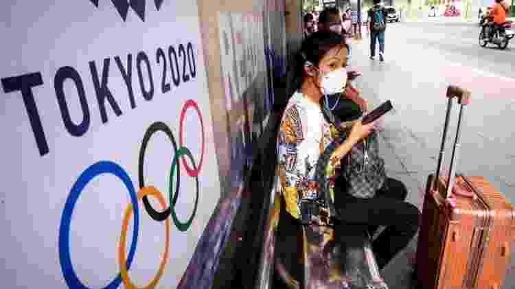 Mulher de máscara no Japão ao lado de logo das Olimpíadas - AFP - AFP