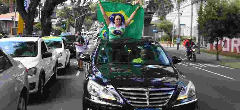 Manifestante segura bandeira do Brasil do lado de fora do teto solar de um Hyundai Genesis 2013 no protesto de ontem em Curitiba (PR); preço de carros usados na carreata gerou ironias - EDUARDO MATYSIAK/FUTURA PRESS/FUTURA PRESS/ESTADÃO CONTEÚDO