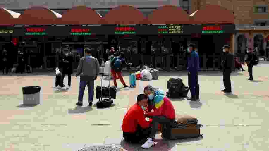 1.abr.2020 - Pessoas usando máscara protetiva contra o coronavírus esperam do lado de fora da Estação Ferroviária de Pequim, na China - Thomas Peter/Reuters