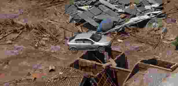 10.nov.2015 - Carro vai parar em cima de uma casa após o rompimento da barragem da Samarco, em Mariana (MG) - Ricardo Moraes/Reuters