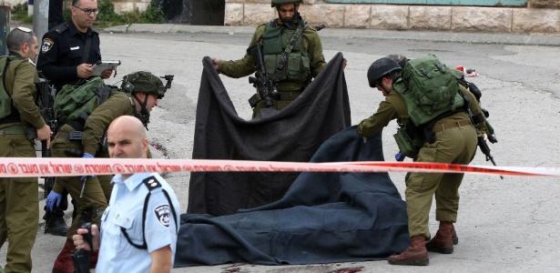 Corpo de palestino que teria sido executado por soldado israelense quando já estava ferido é coberto, em Hebron, na Cisjordânia