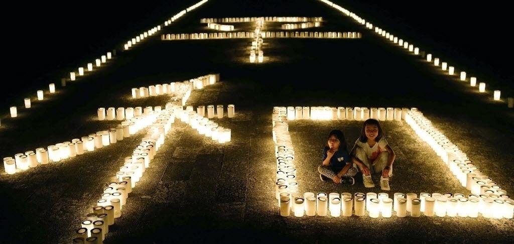 """23.jun.2016 - Velas formam a palavra """"paz"""", em uma homenagem ao 71º aniversário do fim da batalha de Okinawa, no Japão. A batalha foi a maior ação marítima, terrestre e aérea da história, e aconteceu durante a Segunda Guerra Mundial, de abril a junho de 1945"""