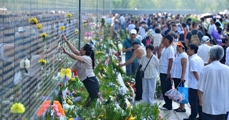 28.jul.2016 - Mulher coloca uma flor ao lado do nome de um familiar morto durante o grande terremoto de 1976 na cidade de Tangshan, no norte da China. Estima-se que o tremor deixou mais de 250 mil mortos. Todos os anos, parentes e amigos vão ao memorial para homenagear as vítimas do terremoto, que completa 40 anos