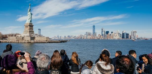 Turistas observam a Estátua da Liberdade