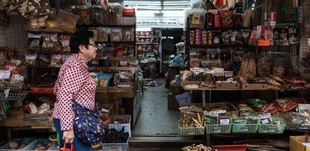 Uma mulher passa por uma loja em uma rua popular para alimentos secos, usados na medicina tradicional chinesa e em pratos em Hong Kong