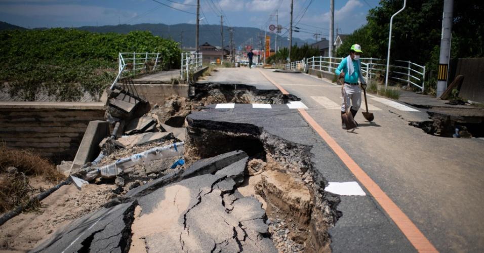 10.jul.2018 - Um homem caminha por uma estrada danificada em uma área inundada