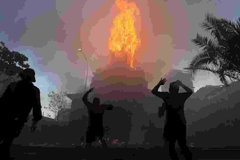 18.out.2020 - Manifestantes encapuzados são vistos nas proximidades da Igreja Assunção, incendiada em meio a protestos em Santiago - EFE/Elvis González