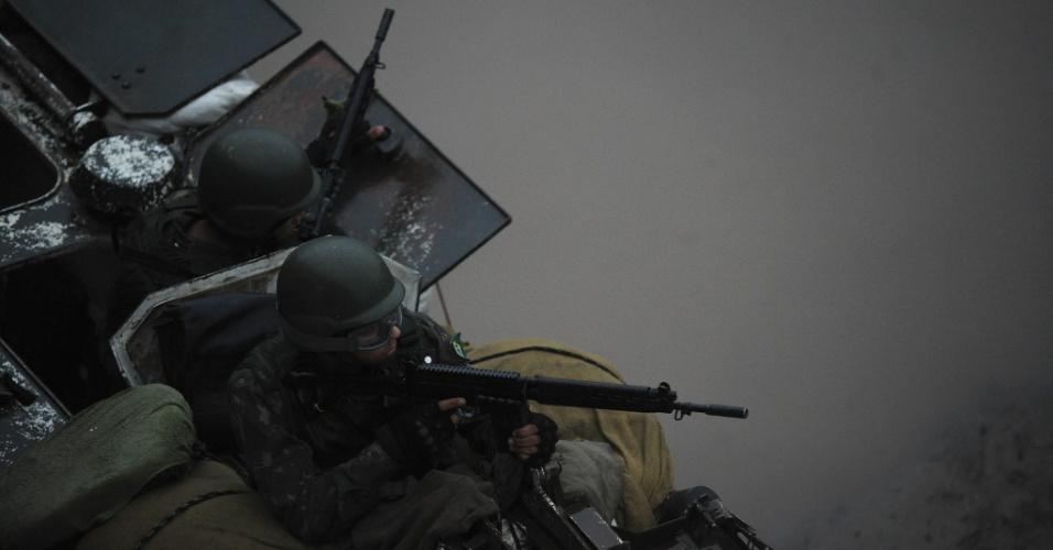 19.jun.2015 - Dentro de tanque, militares das Forças Armadas patrulham rua da comunidade Vila dos Pinheiros, no complexo da Maré, na zona norte do Rio de Janeiro. A Força de Pacificação vai deixar as favelas no dia 30 de junho, após 15 meses de ocupação