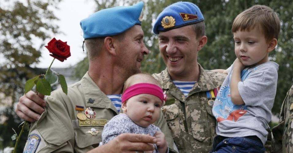 4.ago.2015 - Paraquedistas ucranianos, que retornaram de confrontos na linha de frente no leste do país, seguram seus filhos durante uma cerimônia de boas-vindas, em Kiev