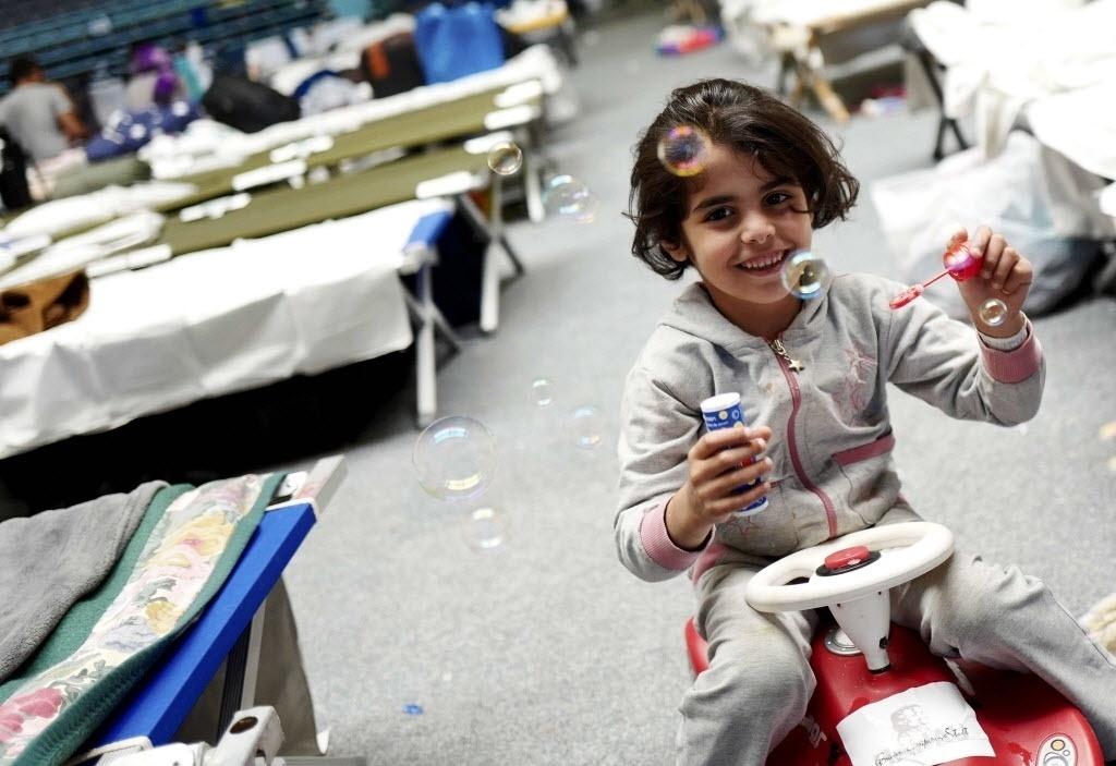29.set.2015 - Garota brinca com bolhas de sabão em um abrigo temporário para migrantes em um salão de esportes em Hanau, na Alemanha