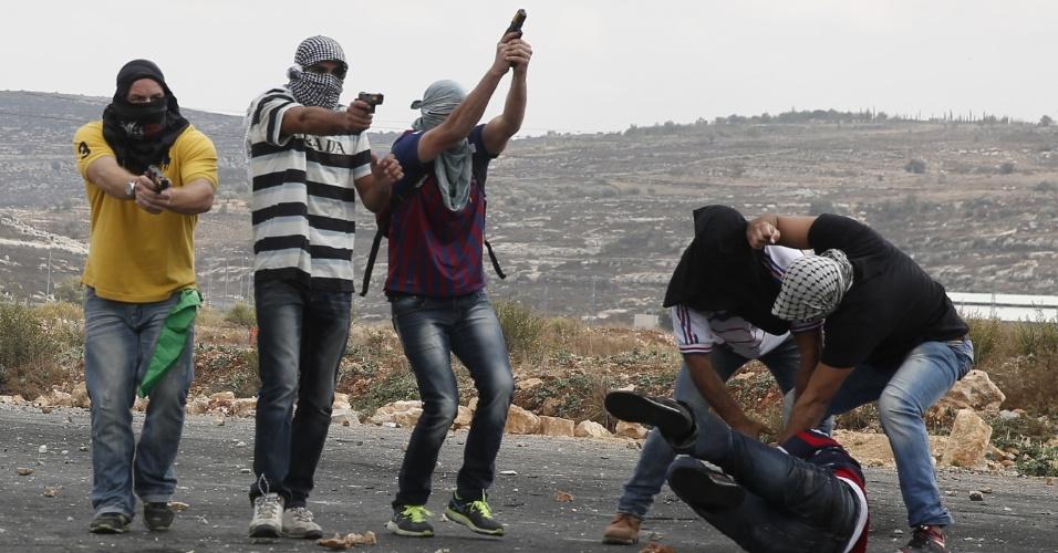 7.out.2015 - Membros infiltrados das forças de segurança israelenses detêm um palestino e apontam suas armas na direção dos manifestantes durante confronto em Beit El, nos arredores da cidade de Ramallah, Cisjordânia. Novos casos de violência entre palestinos e as forças de segurança de Israel aumentam o temor de uma nova Intifada, o conhecido levante palestino