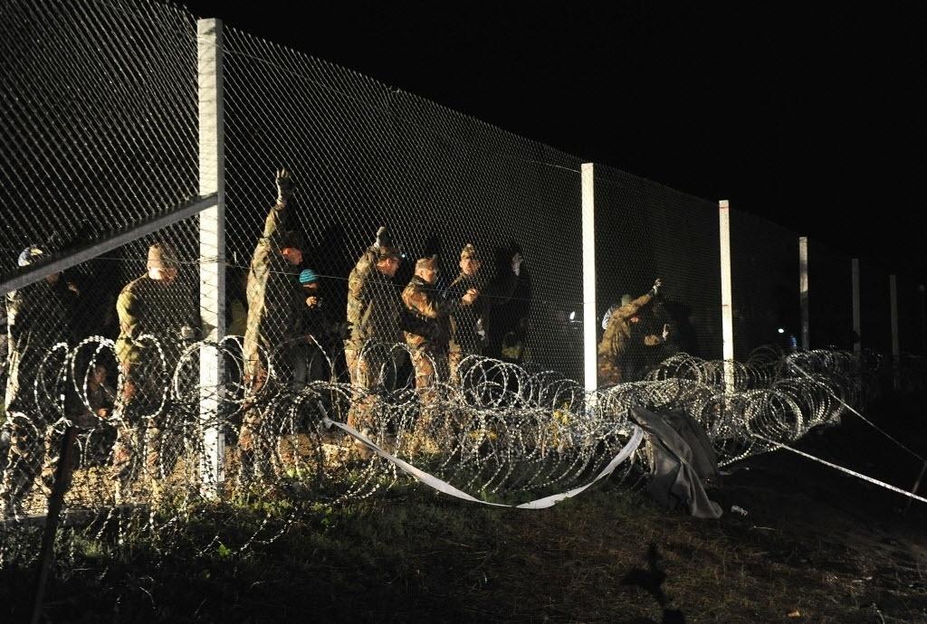 16.out.2015 - Soldados húngaros fecham a fronteira entre a Hungria e a Croácia com arame farpado e uma cerca em Botovo, depois de deixar um último grupo de migrantes passarem.  A medida visa conter o fluxo de milhares de refugiados que chegam diariamente ao país, segundo o ministro de Relações Exteriores húngaro, Peter Szijjarto
