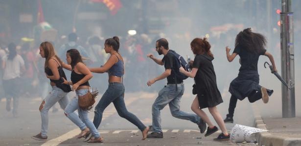 Pessoas tentam escapar da confusão ocorrida no protesto contra o aumento das tarifas de ônibus nesta terça-feira (12)