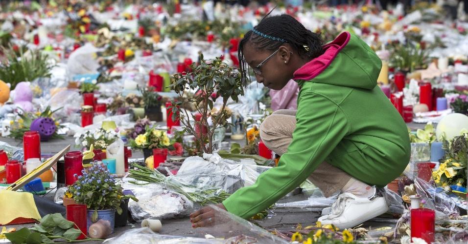 17.abr.2016 - Garota deposita flores em memorial improvisado em homenagem às vítimas do ataque terrorista de 22 de março, em Bruxelas, na Bélgica. O ato faz parte de uma marcha contra o terrorismo e o ódio