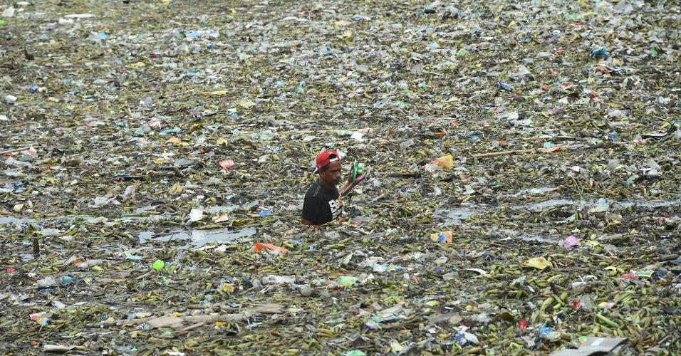 1º.ago.2016 - Homem coleta material reciclável em canal repleto de lixo no centro de Manila, capital das Filipinas