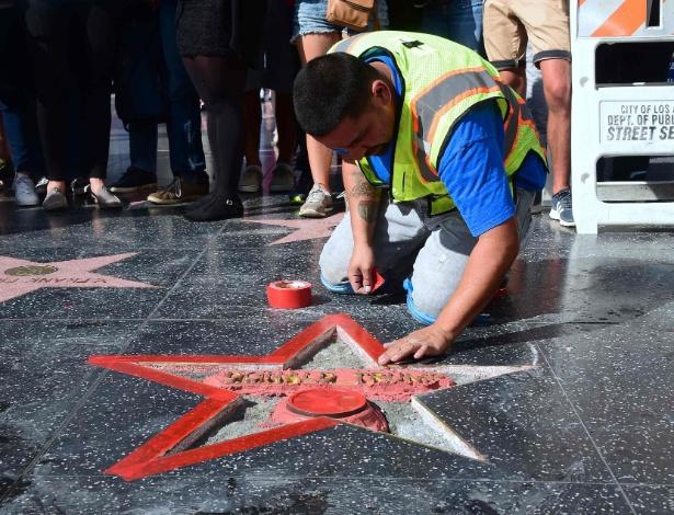 Multidão observa enquanto a estrela de Donald Trump na Calçada da Fama é limpada após ter sido vandalizada, em Hollywood