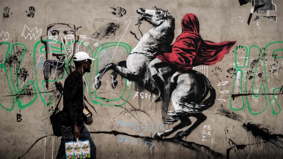 25.jun.2018 - Homem passa em frente a um grafite atribuído ao artista britânico Bansky, nas ruas de Paris - Philippe Lopez/AFP Photo