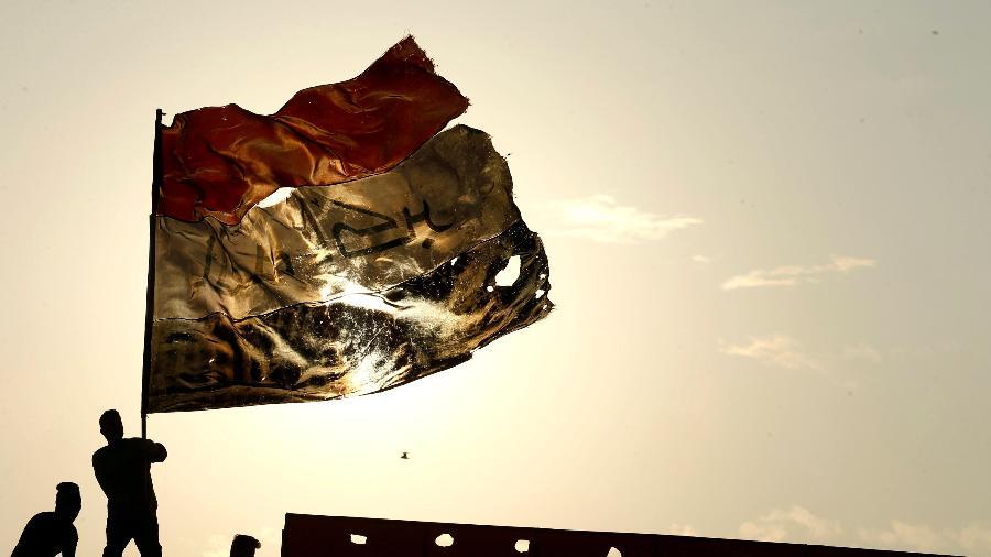 10.dez.2019 - Manifestante segura bandeira do Iraque durante protesto em Bagdá - Alaa al-Marjani/Reuters