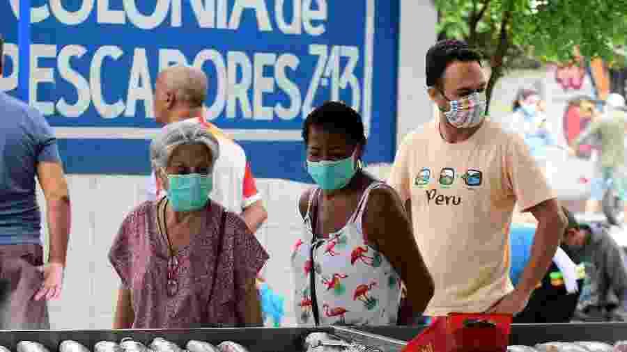 Moradores usam máscaras em área de comércio em Copacabana - PETER ILICCIEV/ ESTADÃO CONTEÚDO