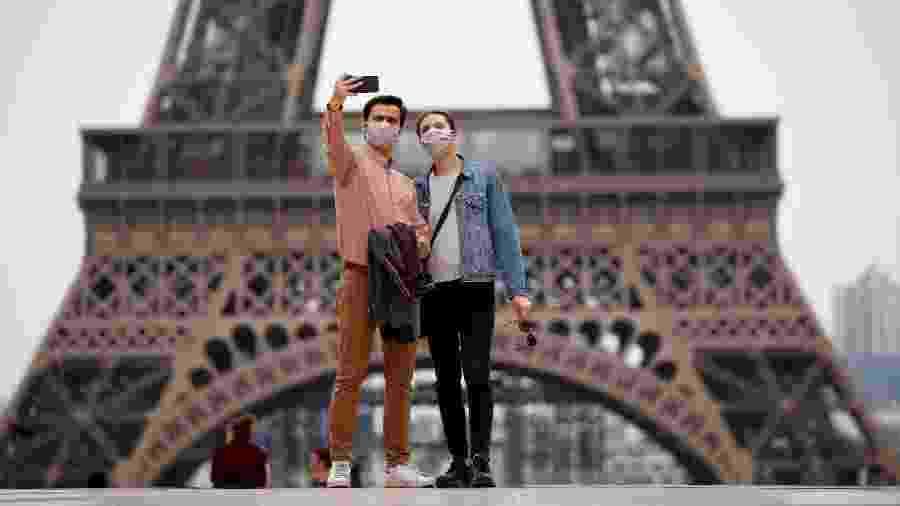 16.mai.2020 - Pessoas usando máscara de proteção enquanto tiram foto em frente à Torre Eiffel, em Paris, na França - Gonzalo Fuentes/Reuters