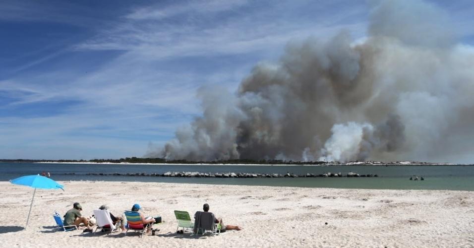 3.mar.2016 - Grupo de amigos vai à praia tomar sol na praia e acaba assistindo incêndio se espalhar pela ilha Shell, no Panamá. A foto foi tirada nesta quarta-feira (2)