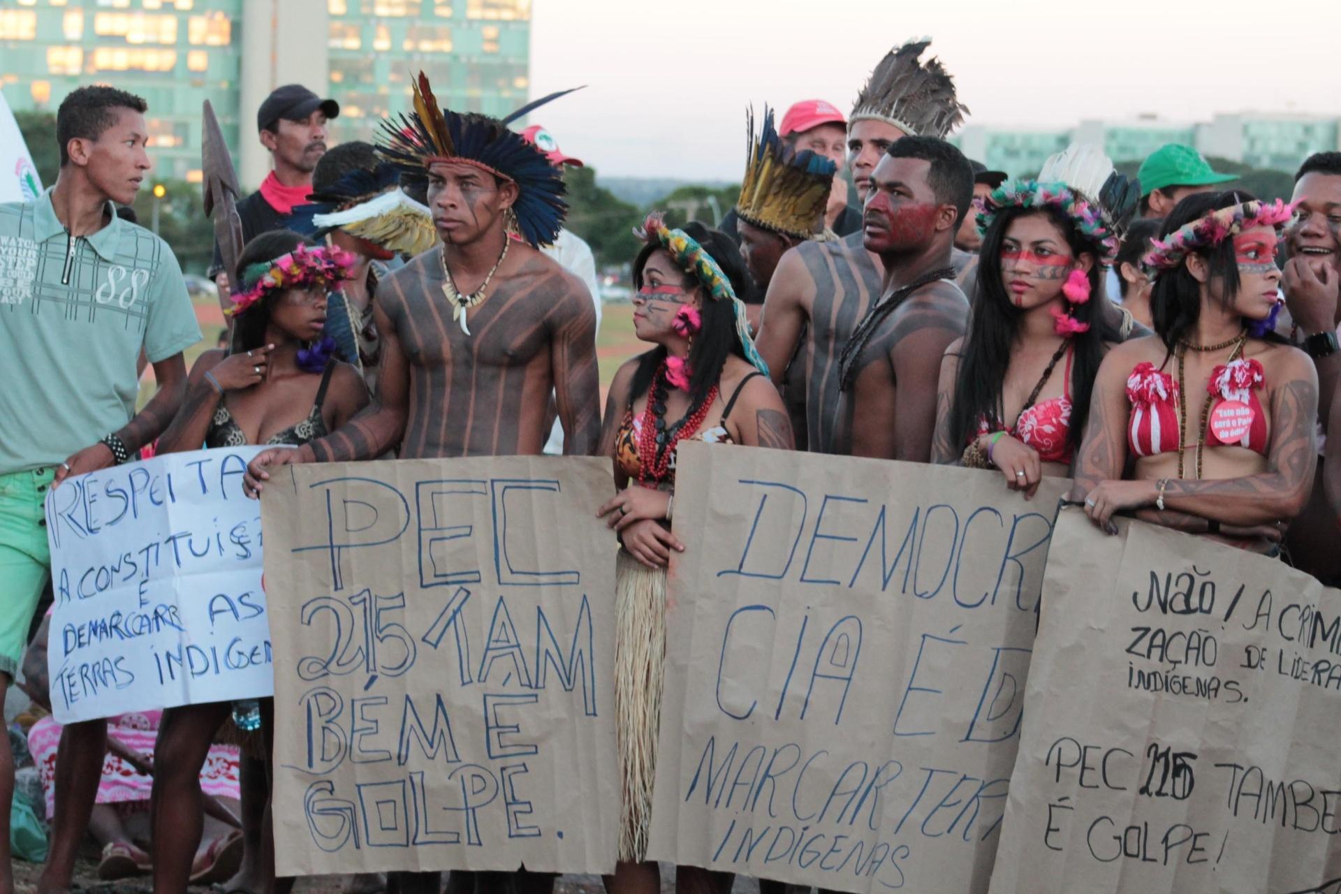 14.abr.2016 - Indígenas participam de manifestação contra o impeachment da presidente Dilma Rousseff, em Brasília. Eles carregam cartazes com mensagem como