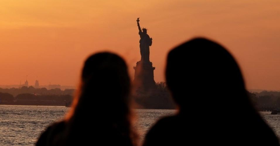 13.mai.2016 - Os turistas que visitam a Estátua da Liberdade nesta tarde, em Nova York, nos EUA, foram recebidos com um lindo pôr do sol