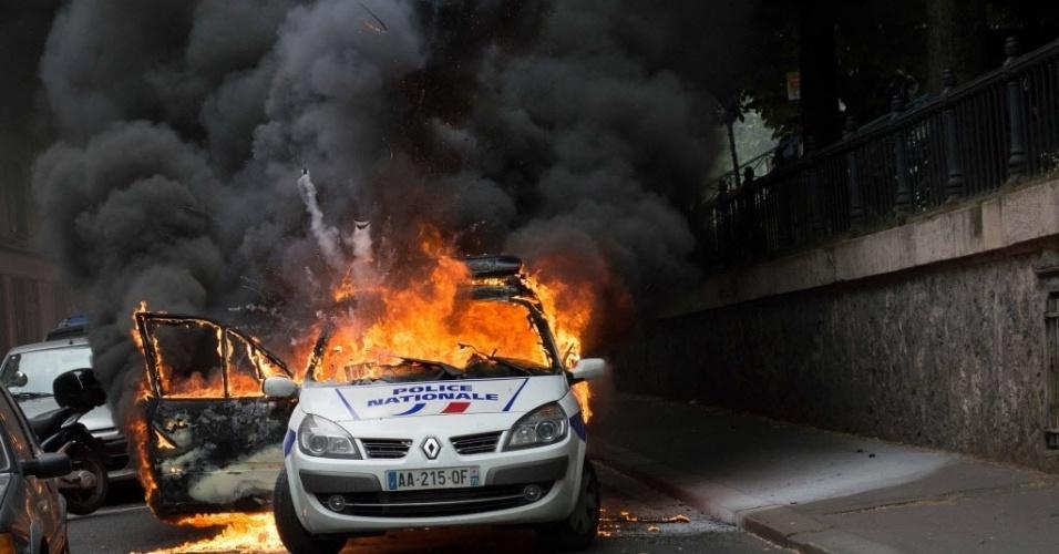 """18.mai.2016 - Um carro da polícia foi incendiado durante uma manifestação contra a violência policial em Paris, na França. Em outro ponto da cidade, autoridades protestaram para denunciar """"o ódio aos policiais"""""""