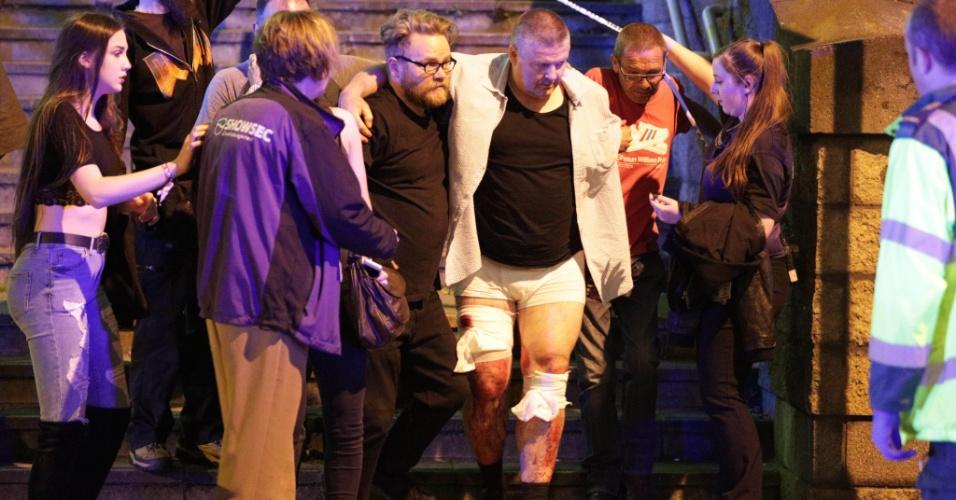 22.mai.2017 - Pessoas ajudam a ferido após explosão na saída da Manchester Arena, em Manchester, Inglaterra