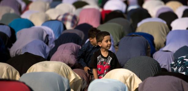 Garoto observa muçulmanos fazendo oração durante o Eid al-Fitr, que marca o fim do Ramadã, o mês mais sagrado para o Islã, em Nova York (EUA)