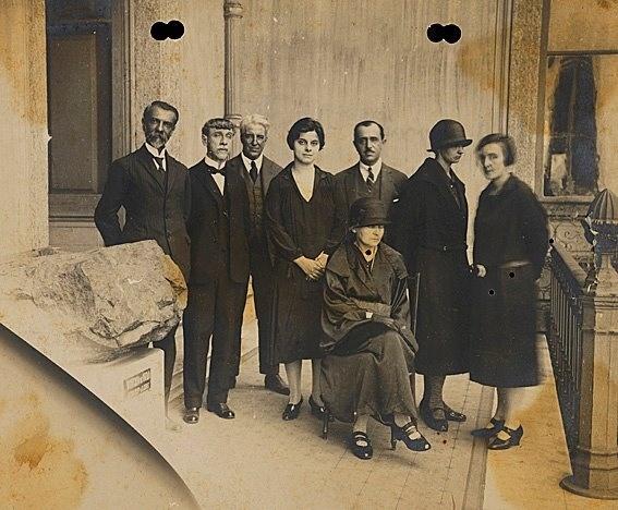 Fotografia Oficial da visita de Madame Curie ao Museu Nacional em 29 de julho de 1926. Identificados, sentada, Madame Curie; de pé, da esquerda para direita: Alípio de Miranda Ribeiro; não identificado; Hermillo Bourguy de Mendonça; Heloísa Alberto Torres, Alberto Betim Paes Leme, Irene Joliot-Currie, filha de Madame Curie e Bertha Lutz.