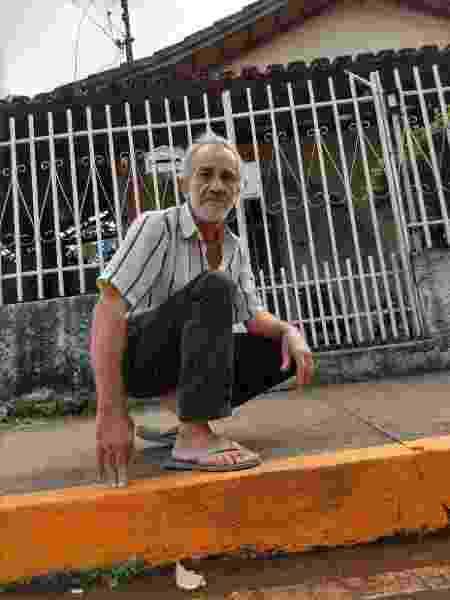 José Mendes, em frente de casa e junto ao meio-fio alaranjado, indicador de que a lama pode ali chegar - Luciana Quierati/UOL