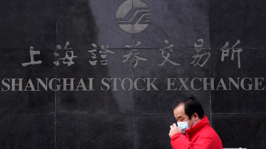 Homem de máscara passa em frente à Bolsa de Valores de Xangai, na China - Aly Song/Reuters