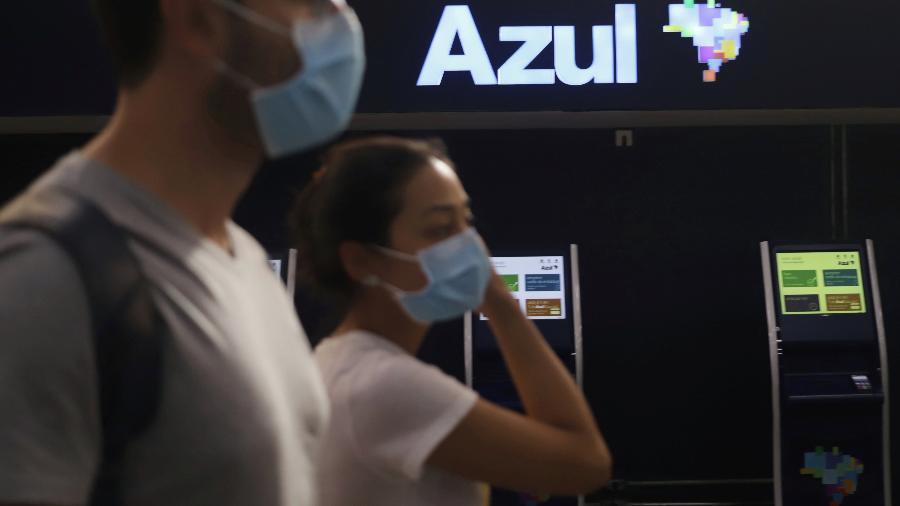 Passageiros com máscaras de proteção caminham em frente a guichês da Azul no aeroporto de Congonhas, em São Paulo - RAHEL PATRASSO