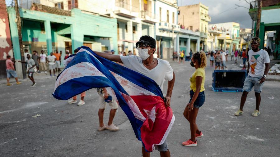 11.jul.2021 - Homem agita bandeira cubana durante uma manifestação contra o governo do presidente cubano Miguel Diaz-Canel, em Havana - Adalberto Roque/AFP